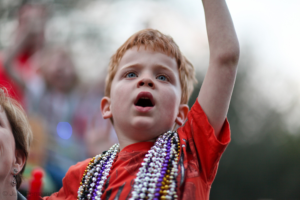 Boy with beads around her neck his caught during the Krewe of Proteus parade .  Mardi Gras 2011 in New Orleans is expected to be have the largest attendance of all time due to the dates overlapping with college spring break. Mardi Gras also known as Carnival begins on or after Epiphany and ending on the day before Ash Wednesday.Mardi Gras 2011 in New Orleans is expected to be have the largest attendance of all time due to the dates overlapping with college spring break. Mardi Gras also known as Carnival begins on or after Epiphany and ending on the day before Ash Wednesday.