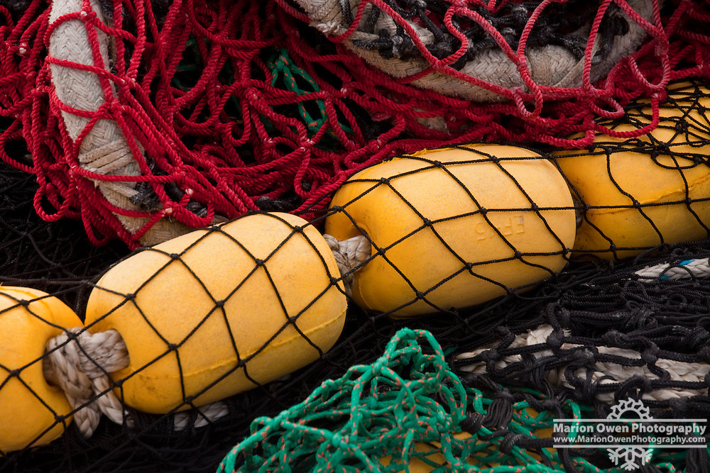 Bright yellow corks contrast the red, black and green net stacked on deck of a commercial fishing vessel in Kodiak, Alaska.