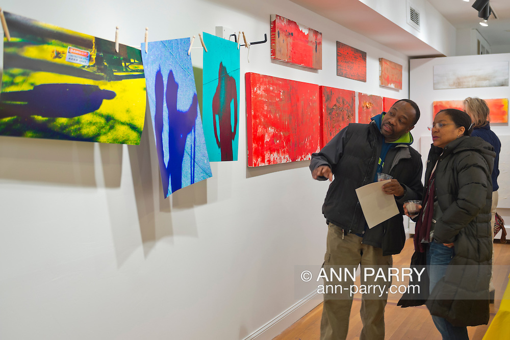Huntington, New York, U.S. - March 1, 2014 - Vistors at the Opening Reception '3 Wild and Crazy Artists' at FotoFoto Gallery discuss the colorful artwork in the exhibit 'Hung Out To Dry' by Thom O'Connor.