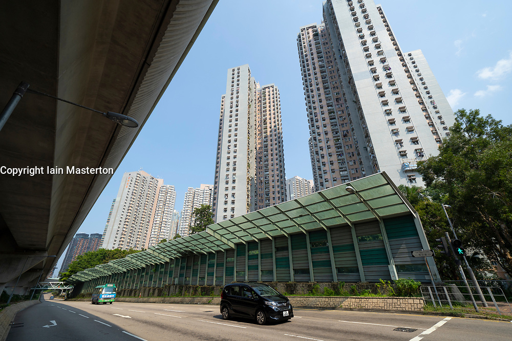 Modern noise barrier wall adjacent to highway and high rise apartment towers in Hong Kong.