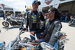 Husband Perry with Fay Keys as she tests out a new Harley-Davidson Softail Deluxe while her husband watches at the Harley-Davidson display at the Speedway during Daytona Bike Week. FL, USA. March 15, 2014.  Photography ©2014 Michael Lichter.