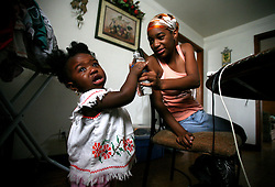09 July 2006. New Orleans. Louisiana. <br /> Finding Faith. <br /> Faith Figueroa. A day in the life of. Faith acts up as she struggles to take a bottle of water from her older sister Jacquelyn.<br /> Following a ten month search for the little girl whose face appeared on the Sept 19th, 2005 cover of Newsweek magazine, Faith's mother, Miriam Figueroa has returned to town with her three children. Faith, (1 yrs), Anfernya (5yrs) and Jacquelyn (13 yrs). <br /> Credit; Charlie Varley/varleypix.com