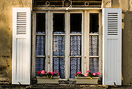 Lace can be seen in the window of a house in Bayeux, France.  Typical flower boxes decorate the sill.