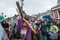 "© Licensed to London News Pictures. 30/03/2018. LONDON, UK.  Jesus, played by James Burke-Dunsmore, carries his cross en route to his crucifixion. The Wintershall Players present their traditional ""The Passion of Jesus"" play in Trafalgar Square on Good Friday in front of large crowds despite the heavy rain.  The play brings to life the events leading to the crucifixion of Jesus Christ, played by James Burke-Dunsmore, and his subsequent resurrection.  Photo credit: Stephen Chung/LNP"