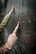 Close-up of the hands of worshipers touching a prayer wall, Lingyin Buddhist temple, Hangzhou, Zhejiang Province, China