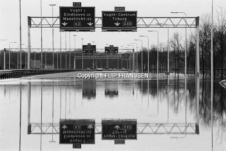 Nederland, Vught, 01-02-1995Eind januari, begin februari 1995 steeg het water van de Rijn, Maas en Waal tot record hoogte van 16,64 m. bij Lobith. Een evacuatie van 250.000 mensen was noodzakelijk vanwege het gevaar voor dijkdoorbraak en overstroming. op verschillende zwakke punten werd geprobeerd de dijken te versterken met zandzakken. Hier is een stuk snelweg bij Den Bosch onder water gekomen.Late January, early February 1995 increased the water of the Rhine, Maas and Waal to a record high of 16.64 meters at Lobith. An evacuation of 250,000 people was needed because of flood risk. At several points people tried to reinforce the dikes with sandbags. Foto: Flip Franssen/Hollandse Hoogte