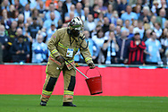 A Fireman removes an object off the Wembley pitch. The Emirates FA Cup semi-final match, Arsenal v Manchester city at Wembley Stadium in London on Sunday 23rd April 2017.<br /> pic by Andrew Orchard,  Andrew Orchard sports photography.