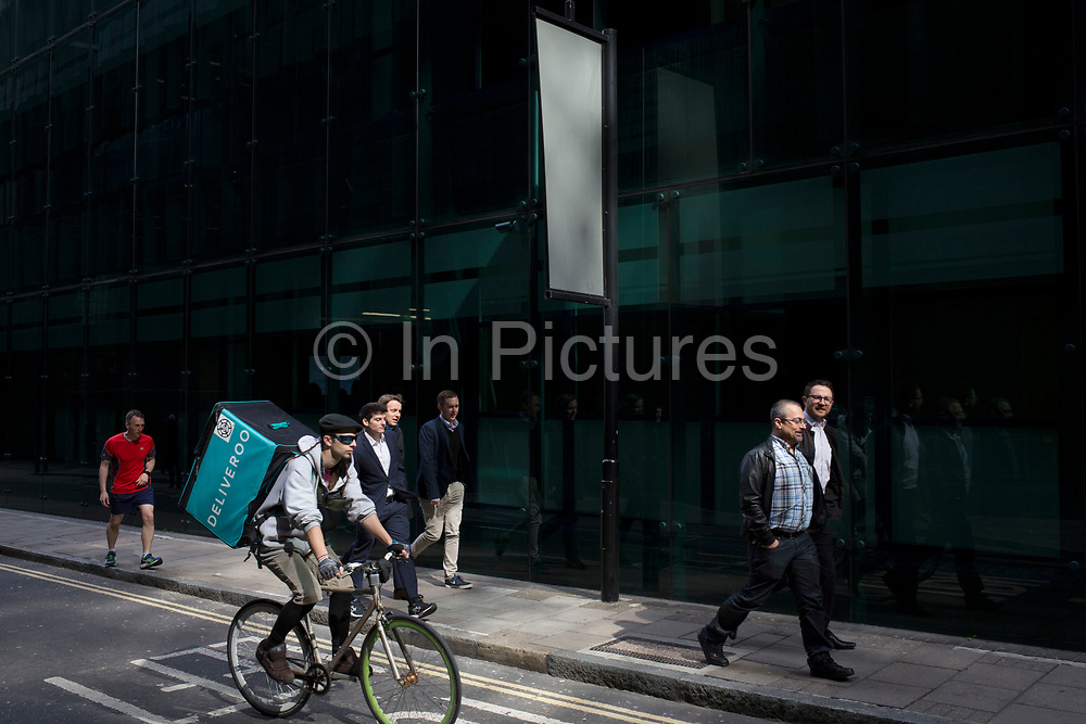 Deliveroo cycle courier with his large back box while out delivering in London, England, United Kingdom.