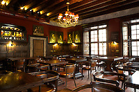 Interior design of Mons Spius restaurant in Lviv, Ukraine. Large dining area with wooden furniture and old paintings on the wall.
