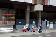 Visitors to London pull their wheelie baggage behind them in Aldgate, on 29th July 2019, in London, England.