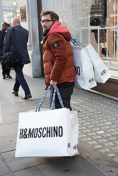 © Licensed to London News Pictures. 08/11/2018. London, UK. A customer leaves the HM store in Oxford Circus with shopping bags of items from the Jeremy Scott H&M X Moschino collection. Photo credit: Ray Tang/LNP