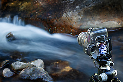 Photographer and small cascades on Elk Creek, Vermejo Park Ranch, New Mexico, USA.