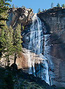 The waterfall of Nevada Fall plunges 594 feet (181 meters) on the Merced River in Yosemite National Park, California, USA. Starting at Happy Isles trail head in Yosemite Valley, hike the steep Mist Trail 2.7 miles with 2000 feet gain to the top of Vernal Fall, via Vernal Fall and Emerald Pool. Return in 3 miles via the John Muir Trail and Clark Point, a favorite loop hike. 100 million years ago, the Sierra Nevada crystallized into granite from magma 5 miles underground. The range started uplifting 4 million years ago, and glaciers eroded the landscape seen today in Yosemite National Park.