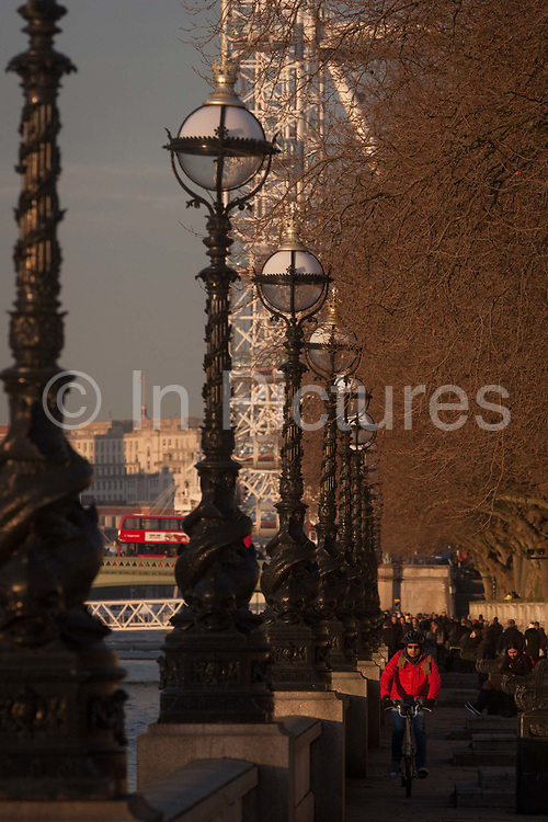 A cyclist rides along The Queens Walk on the south bank of the River Thames, with the London Eye and buses crossing Westminster Bridge, on 18th January 2017, in London England.