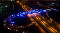 Aerial view of the illuminated Meydan bridge at night in Dubai, United Arab Emirates.