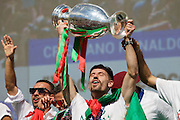 Portuguese player Adrien holding the Euro Cup while celebrating with supporters at Alameda Dom Afonso Henriques, in Lisbon. Portugal's national squad won the Euro Cup the day before, beating in the final France, the organizing country of the European Football Championship, in a match that ended 1-0 after extra-time.