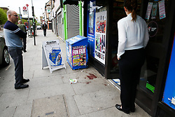 © Licensed to London News Pictures. 25/04/2019. London, UK. People view the blood stains outside Hill's New Point newsagent on Leytonstone High Road, Waltham Forest in East London. Two men were stabbed multiple times at a bus stop next to Hill's New Point newsagent close to Leytonstone High Road overground station just before 8pm on Wednesday 24 April 2019. A man in his 20s remains in a hospital in a critical condition. Photo credit: Dinendra Haria/LNP
