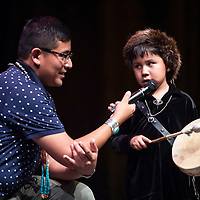 Robert S. John, 5, Navajo, looks at Master of Ceremonies J.T. Willie while performing during the Tiny Tot Pageant at El Morro Theatre, Monday, August 6, 2018.