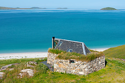 Small old croft cottage converted into modern house on island of Eriskay overlooking Sound of Barra, Scotland, UK