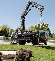 "With the use of his crane Stephen Green swings his 2000 lb granite sculpture ""Advantage"" into position at Hesky Park on Tuesday afternoon as the second installation for the Greater Meredith Program's Sculpture Walk.   (Karen Bobotas/for the Laconia Daily Sun)"