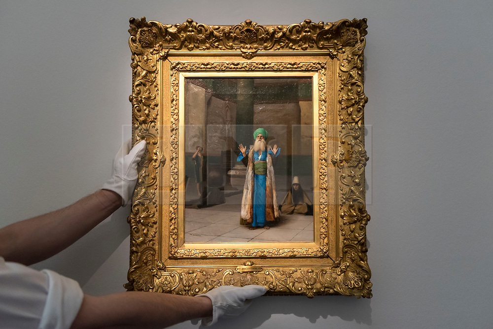 """© Licensed to London News Pictures. 20/04/2018. LONDON, UK. A technician presents """"A Sultan at Prayer"""" by Jean-Léon Gérôme (Est. 200-300k) at a preview of works in Sotheby's 20th Century Middle East, Orientalist and Islamic upcoming art sales in New Bond Street.  The works will be sold at auction in the last week of April.    Photo credit: Stephen Chung/LNP"""