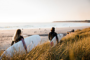 Surfers holding surfboards walking through the sand dunes at Le Braye, St Ouen's Bay, Jersey, ready to go surfing.
