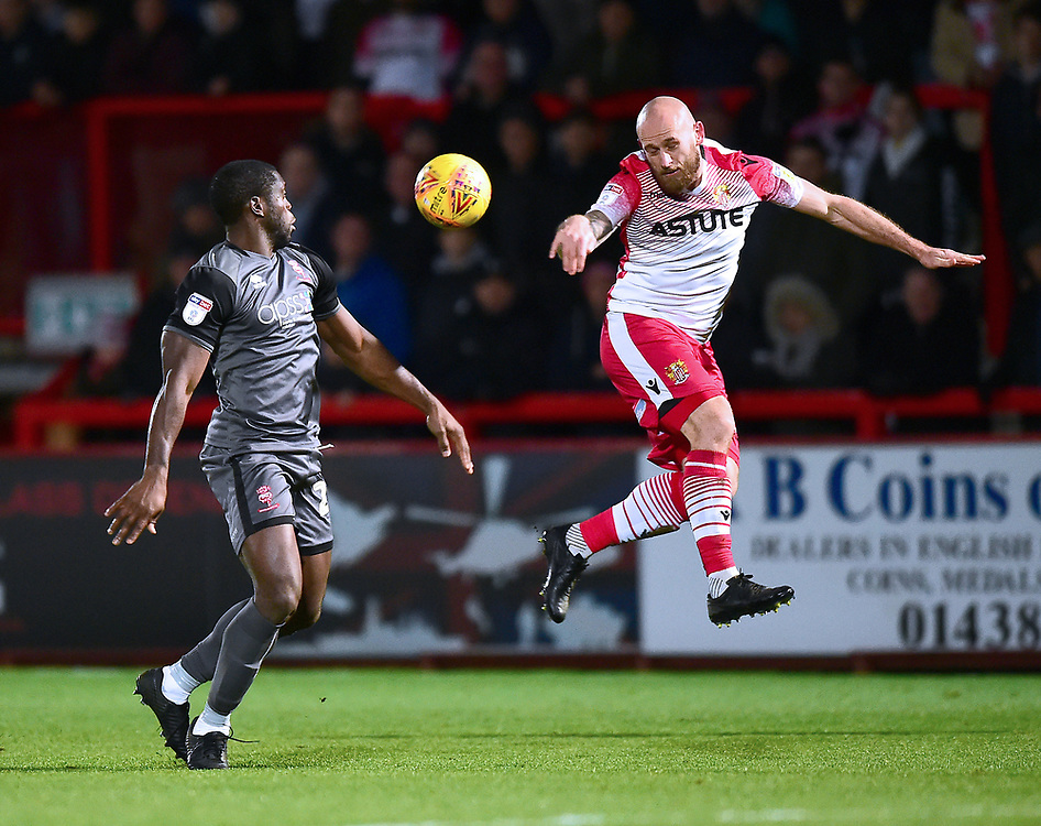 Stevenage's Scott Cuthbert clears under pressure from  Lincoln City's John Akinde<br /> <br /> Photographer Andrew Vaughan/CameraSport<br /> <br /> The EFL Sky Bet League Two - Stevenage v Lincoln City - Saturday 8th December 2018 - The Lamex Stadium - Stevenage<br /> <br /> World Copyright © 2018 CameraSport. All rights reserved. 43 Linden Ave. Countesthorpe. Leicester. England. LE8 5PG - Tel: +44 (0) 116 277 4147 - admin@camerasport.com - www.camerasport.com