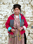 Portrait of a Brokpa woman wearing her traditional clothing outside the temple on an 'auspicious day' in the remote village of Merak in Eastern Bhutan. The Brokpa, the semi-nomads of the villages of Merak and Sakteng are said to have migrated to Bhutan a few centuries ago from the Tshona region of Southern Tibet. Thriving on rearing yaks and sheep, the Brokpas have maintained many of their unique traditions and customs. Their distinctive hat known as 'tsipee cham' is made of yak felt with long twisted tufts, said to keep the rain from running onto their faces.