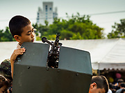 """13 JANUARY 2018 - BANGKOK, THAILAND:      A Thai child looks at a FN Mag machine gun mounted on a Thai Army jeep during Children's Day activities at the Royal Thai Army's King's Guard 2nd Cavalry Camp in central Bangkok. Children's Day is called """"Wan Dek"""" in Thai. Many government offices and military bases hold special activities for children as do shopping malls.    PHOTO BY JACK KURTZ"""