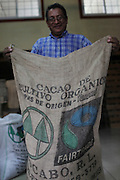 José Howell, receiving manager for COCABO, holds a cocoa beans sack with the Fair Trade logo on it. COCABO: Almirante, Changuinola, Bocas del Toro, Panamá. September 1, 2012.