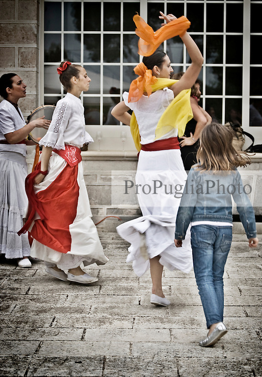 """Una piccola spettatrice viene coinvolta a ballare con una ballerina del gruppo musicale di Pizzica """"Arakne Mediterranea"""" durante un concerto a """"Castello Monaci"""" nei pressi di Salice Salentino in provincia di Lecce. 30/05/2010 (PH Gabriele Spedicato)..People dancing with the dancers of """"Arakne Mediterranea""""during the concert in """"Castello Monaci"""" near Salice Salentino, a Town in province of Lecce.30/05/2010 PH Gabriele Spedicato..La pizzica, o, detta nella sua forma più tradizionale pizzica pizzica, è una danza popolare attribuita oggi particolarmente al Salento, ma in realtà era praticata sino agli anni '70 del XX sec. in tutta la Puglia centro-meridionale e in Basilicata..Fa parte della grande famiglia delle tarantelle, come si usa chiamare quel variegato gruppo di danze diffuse dall'Età Moderna nell'Italia meridionale"""