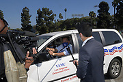 KNBC4 News reporter Ted Chen (right) conducts an interview at the Los Angeles Dodgers Foundation 16th annual Thanksgiving Turkey Giveaway at Dodger Stadium, Thursday, Nov. 19, 2020, in Los Angeles.