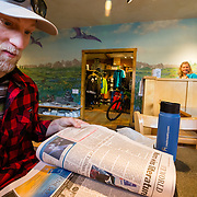 Andrew Whiteford reads the paper at Pearl Street Bagels next door to Wilson Backcountry Sports in Wilson, Wyoming.