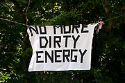 Balcombe, West Sussex. Site of Cuadrilla drilling . A banner hung in the trees says 'No more dirty energy'.