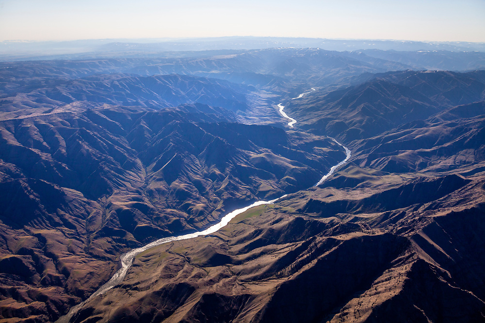 Aerial of the Snake River in Hells Canyon flowing in from the south creating the Idaho - Washington border through mountainous terrain. Licensing - Open Edition Print