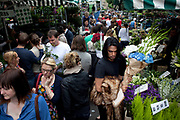 Buyers and sellers at East London's famous Sunday flower market on Columbia Road. Punters come here from the early hours to snatch up the best of the plants offered, and latecomers also can snap up a few last minute bargains. Columbia Road is one of four local Sunday markets in this area of the East End of London, England, UK.
