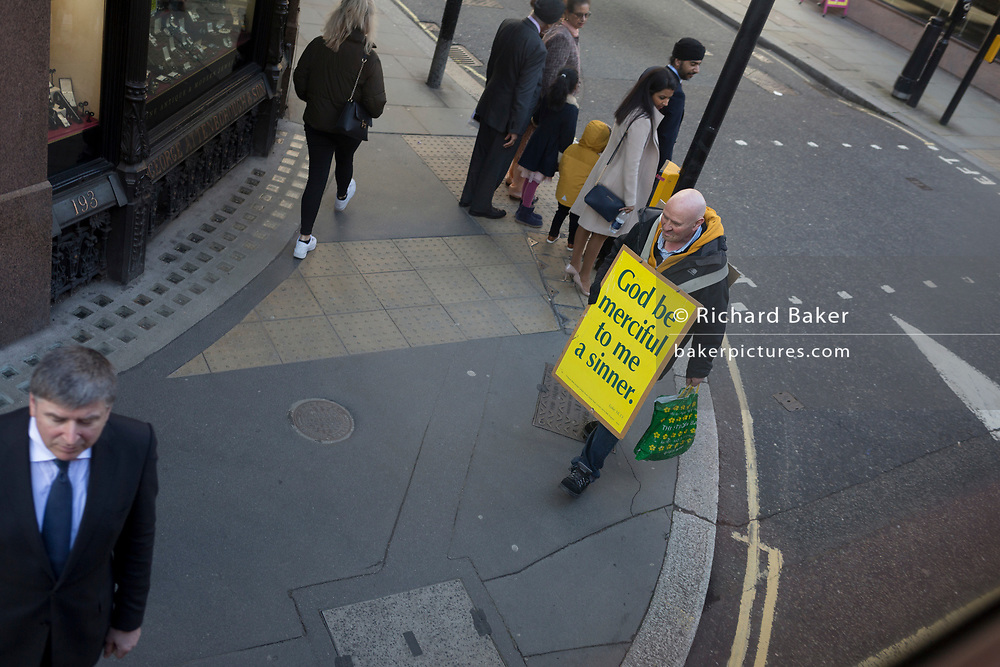 A Christian man carries a placard proclaiming that his God should be merciful for his own sins, as he walks towards a businessman waiting to cross Fleet Street in the capital's financial district, the City of London, on 11th March 2020, in London, England.