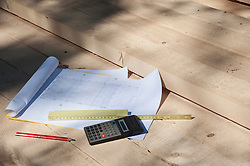 Blue print, ruler and calculator on wood