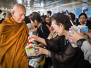 """29 NOVEMBER 2016 - BANGKOK, THAILAND:  Buddhist monks collect alms from people during a special """"tak bat"""" or merit making ceremony in the Ratchaprasong skywalk of the Bangkok BTS system. The tak bat was to honor Bhumibol Adulyadej, the Late King of Thailand. Food and other goods were given to the monks, who in turn gave the items to charities that will distribute them to Bangkok's poor. More than 100 Buddhist monks participated in the merit making ceremony. The ceremony was organized by the merchants in the Ratchaprasong Intersection, which includes some of Bangkok's most upscale shopping centers.     PHOTO BY JACK KURTZ"""