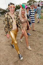 © Licensed to London News Pictures. 06/09/2014. Isle of Wight, UK. Festival goers at Bestival 2014 Day 3 Saturday in fancy dress costume - the man in gold is a rockstar with a huge fake penis in his leggings.   Today is the festival's Fancy Dress Day - this year the theme is Desert Island Disco.  Festival goers spend the morning readying their costumes before the judging of the competition at 2pm.  This weekend's headliners include Chic featuring Nile Rodgers, Foals and Outcast.   Bestival is a four-day music festival held at the Robin Hill country park on the Isle of Wight, England. It has been held annually in late summer since 2004.    Photo credit : Richard Isaac/LNP