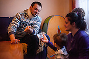 Former refugee Elvis Causevic with his wife Irma and their children Adna (3 1/2) and Aldin (1 1/2) in the living room at the  families house in Hadžići. The family settled here after the war ended in Bosnia. Hadžići is a town and a municipality located about 20 km south west of Sarajevo city but within the Sarajevo Canton of Bosnia and Herzegovina. According to the census of 2013, Hadžići municipality has a population of 23,891 residents.