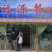 A Chinese couple stands in the door of their new roadside restaurant and truck stop between Nyingchi and Lhasa, Tibet.  The painted sign reads in both Tibetan (above) and Chinese.