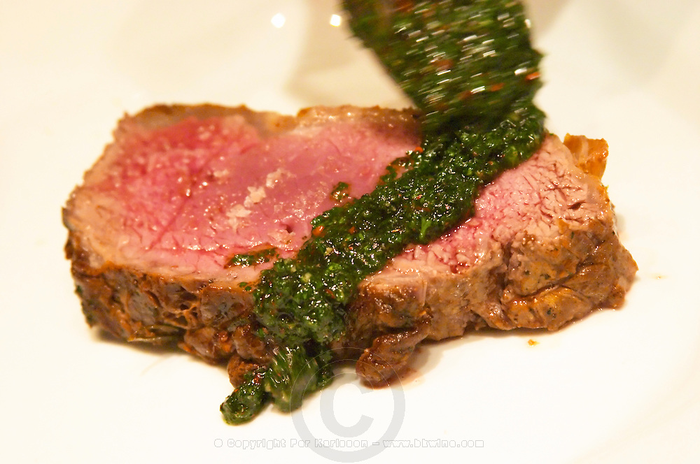 A slice of juicy red roast beef with a cook placing green herb sauce on it. The Dolly Irigoyen - famous chef and TV presenter - private restaurant, Buenos Aires Argentina, South America Espacio Dolli