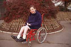 Teenage girl with disability; who is wheelchair user; wearing school uniform smiling,
