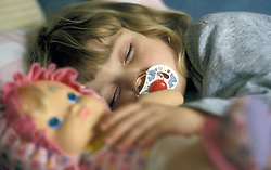 Small girl asleep with dummy clutching doll UK