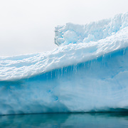 Small icicles hang from a ledge of an iceberg.