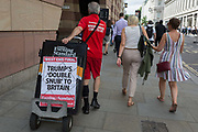 An Evening Standard newspaper vendor pulls his stand with yesterdays headline for the previous days West End final edition, about US President Trumps controversial comments about Prime Minister Theresa Mays handling of Brexit, and the leaked messages of British ambassador to Washington, Kim Darroch who resigned the next day, in the City of London, the capitals financial district aka the Square Mile, on 10th July 2019, in London England.