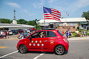 A man drives a small red car with an American flag in the Independence Day parade in Millville, Pennsylvania on July 5, 2021.