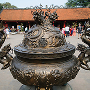 A heavy bronze urn for burning incense at the Temple of Literature in Hanoi, Vietnam. The Temple is a center of learning and scholarship dedicated to Confucius and first established in 1070. The temple was built in 1070 and is one of several temples in Vietnam which are dedicated to Confucius, sages and scholars.