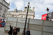 """A pedestrian points towards a London site next to a temporary construction hoarding beneath the partially hidden statue of the world famous London Victorian-era landmark, Eros in Piccadilly Circus, on 25th February 2020, in London, England. Eros, or the Shaftesbury Memorial Fountain is located at the southeastern side of Piccadilly Circus in London, United Kingdom. Moved after World War II from its original position in the centre, it was erected in 1892–1893 to commemorate the philanthropic works of Lord Shaftesbury, who was a famous Victorian politician and philanthropist. The monument is surmounted by Alfred Gilbert's winged nude statue generally, though mistakenly, known as Eros. This has been called """"London's most famous work of sculpture."""""""